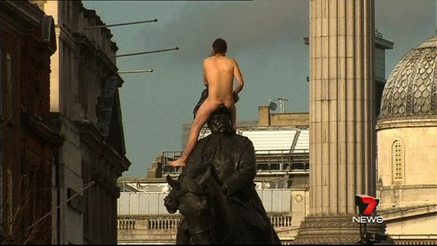 Nude protester straddles London statue
