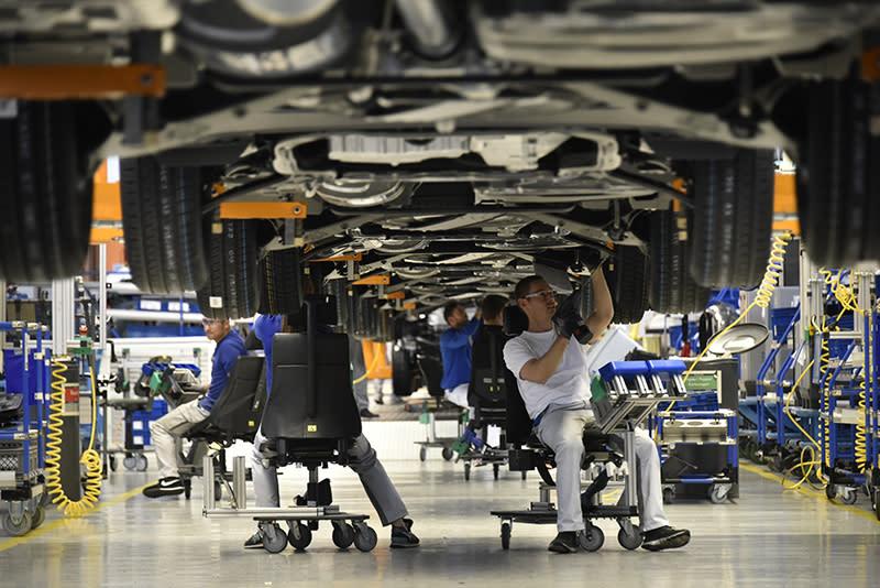 底盤部件則由工人乘坐輔具組裝,以確保生產線效率。