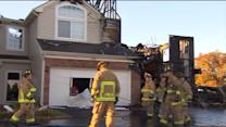 Townhouse bursts into flame after car crashes into it