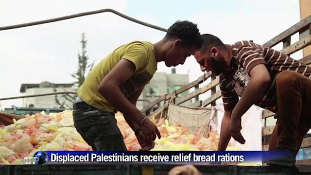 Displaced Palestinians receive relief bread rations